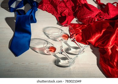 Female red underwear, dress , male tie and glass of wine on the floor, a symbol of romance and sex