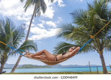 Female relaxing in a hammock on a tropical beach. Enjoying beach life on Palawan island, Philippines