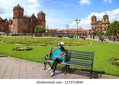 Female relaxing on a bench at Plaza de Armas with Cusco Cathedral and the Iglesia de la Compania de Jesus in background, Cusco, Peru