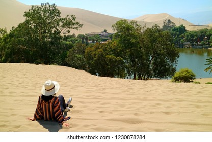 Female relaxing on the sand dune, admiring the oasis town of Huacachina, Ica, Peru