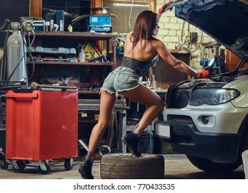 Female repairing a car.