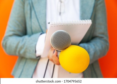 Female reporter at press conference or media event, writing notes, holding microphone. Journalism concept.