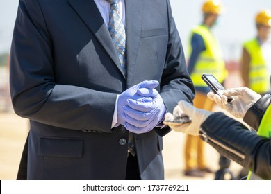 Female reporter wearing protective gloves against coronavirus COVID-19 disease and holding voice recorder making media interview with politician or business person during virus pandemic