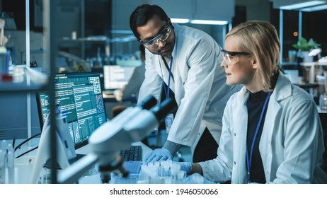 Female Research Scientist Has a Conversation with Bioengineer About the Latest DNA Experiments in a Modern Laboratory. She is Doing Important Medical Research with Help of Modern Computer Software.