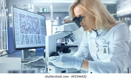 Female Research Scientist Looks at Biological Samples Under Microscope. She and Her Colleagues Work in a Big Modern Laboratory/ Medical Centre.