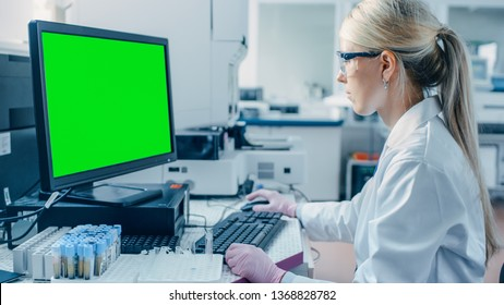 Female Research Scientist Sits at His Workplace in Laboratory, Uses Green Mock-up Screen Personal Computer. In the Background Genetics, Pharmaceutical Research Centre.