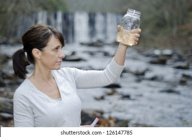 Female researcher checking the water quality from a river