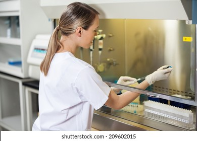 Female researcher filling liquid in testtube at laboratory