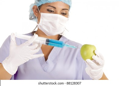 female researcher injecting liquid in green apple
