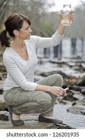 Female researcher testing the water quality in a river