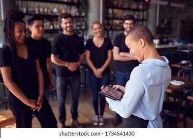 Female Restaurant Manager With Digital Tablet Giving Team Talk To Waiting Staff