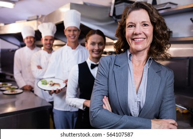 Female restaurant manager standing in front of team of staff smiling at camera