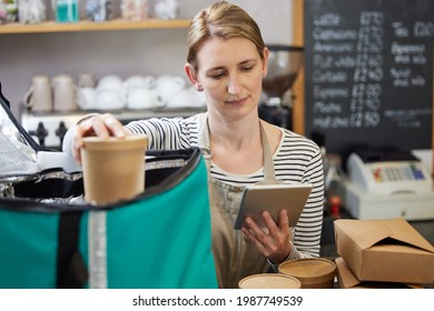 Female Restaurant Worker With Digital Tablet Packing Insulated Bag For Takeaway Food Home Delivery