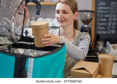 Female Restaurant Worker Packing Insulated Bag For Takeaway Food Home Delivery