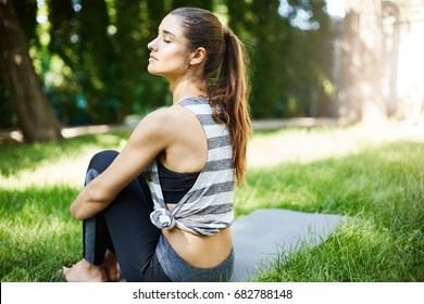 Female resting after an outdoor group training breathing deep. Yoga or pilates practice.