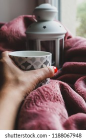 Female resting on the sofa under the blanket and holding in her hand a cup of hot tea and looking through the window. Concept of home cosiness, lazy sunday, relax lifestyle