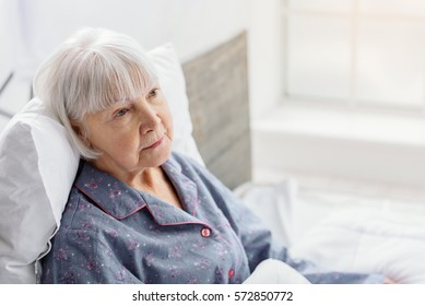 Female retiree lying in bright apartment of clinic