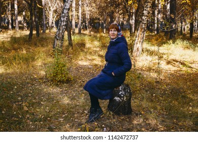 female retirement age sitting on a tree stump in a forest in autumn