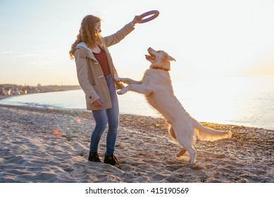 female with retriever dog playing on the beach during sunset or sunrise