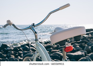 Female retro bicycle on the beach on a background of blue sea on a sunny day, close-up