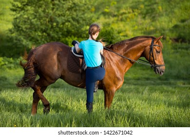 Female rider mounting her thoroughbred horse at riding stables