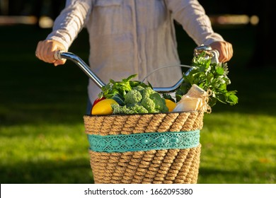 Female riding a bike with fresh vegetables from market, green grass background