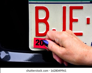 A female right hand applying the required annual license registration on rear license plate with the number 20 showing on the tag.