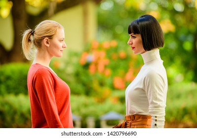 Female rivalry. Friendship problems rivalry and jealousy. Rivalry and leadership. Women looking at each other with attention. Blonde brunette competitors. Pretty girls friends sisters. Eye contact.