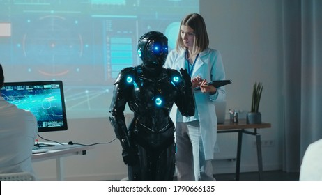 Female robotics engineer control automated robot with digital tablet giving commands. Multi-ethnic team of researchers working in high tech scientific laboratory.