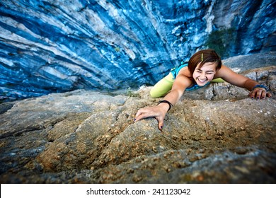 female rock climber climbs on a rocky wall, Keep a hand on the rock and laughs. focus on the hand