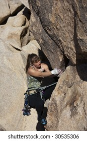 Female rock climber is focused on the next move as she battles her way up a steep cliff in Joshua Tree National Park, California.
