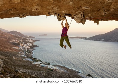 Female rock climber on challenging route in cave at sunset