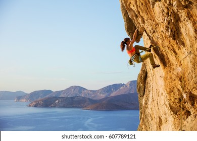 Female rock climber on challenging route on cliff, view of coast below