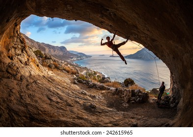Female rock climber posing while climbing along roof in cave at sunset