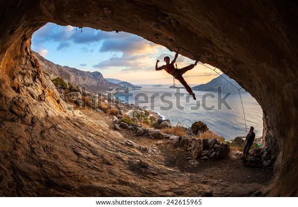 Female Rock Climber Dangling On Edge Stock Photo (Edit Now
