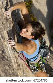 Female rock climber struggles for her next grip on the edge of a steep cliff.