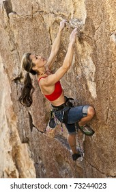 Female rock climber struggles to reach her next grip as she battles her way up a steep cliff in Joshua Tree National Park, California.