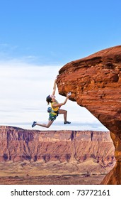 Female rock climber struggles to reach her next grip as she battles her way up a steep cliff.