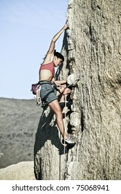Female rock climber struggles to reach her next grip on a challenging ascent.
