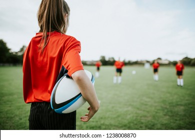 Female rugby player holding the ball in her arms