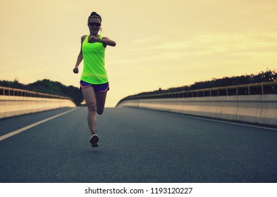 Female Runner athlete running on road. woman fitness jogging workout wellness concept