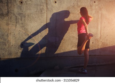 Female runner with beautiful figure doing stretching exercise before began her run, athletic woman warming up outdoors against concrete wall with copy space area for your text message or content