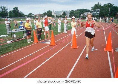 A female runner crossing the finish line at the Senior Olympics, St. Louis, MO