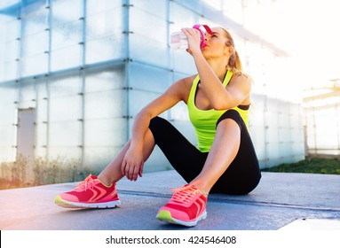 Female runner drinking water after workout