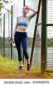 Female runner during outdoor workout in a Park. Beautiful fit redhead girl. Fitness model outdoors. Resting after workout. Holding fruit infuser water bottle.  Healthy lifestyle.