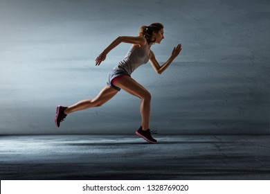 female runner in front of concrete wall