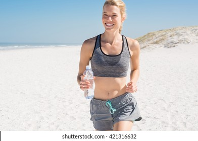 Female runner jogging during outdoor workout on beach. Smiling woman running on beach. Beautiful fitness girl exercising outdoors with sea background.