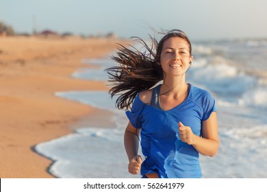 Female runner jogging during outdoor workout on beach listening to music in earphones. Healthy active lifestyle girl