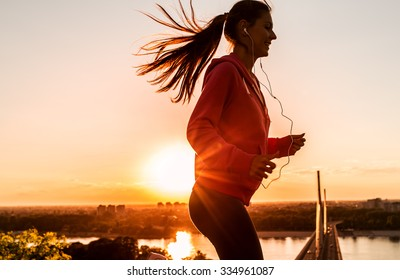 Female runner jogging on beautiful sunset. City scape in background.