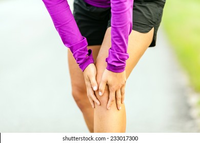 Female runner leg and muscle pain during running outdoors in summer nature, sport jogging physical injury working out outside holding sore knee joint. Health and fitness concept accident when training